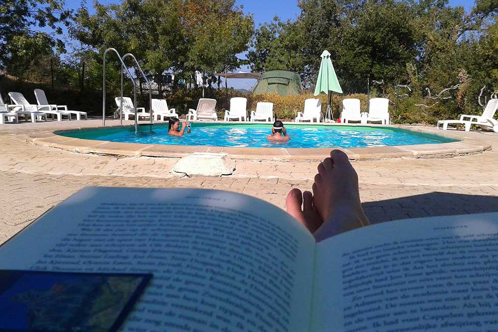 Reading by the pool in quiet rural camping